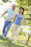 Couples fonctionnant à l'extérieur dans le sourire de stationnement Images libres de droits