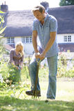 Couples fonctionnant dans le jardin à la maison ensemble photo stock