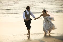 Couples fonctionnant en bas de la plage. Photos libres de droits