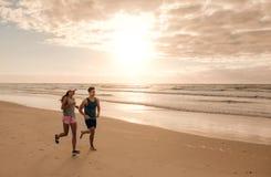 Couples fonctionnant ensemble sur le bord de mer Images stock