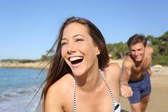 Couples fonctionnant et jouant sur la plage Photographie stock libre de droits
