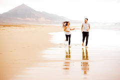 Couples fonctionnant sur la belle plage Images libres de droits