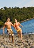 Couples fonctionnant sur la plage Photos libres de droits