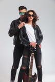 Couples frais dans des vestes en cuir se tenant embrassées tenant l'electri Photos libres de droits