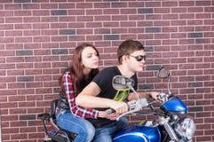 Couples frais sur la moto devant le mur de briques Photographie stock libre de droits