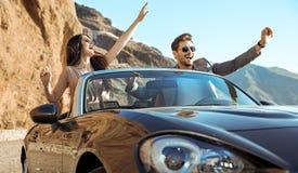 Couples futés montant un convertible luxueux Photos stock