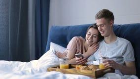 Couples gais appréciant le petit déjeuner romantique dans le lit clips vidéos