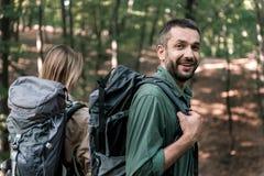 Couples gais augmentant dans la forêt avec des sacs à dos Images libres de droits