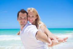 Couples gais ayant l'amusement à la plage un jour ensoleillé Photo stock