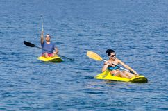 Couples gais barbotant dans le kayak en mer ionienne photo stock