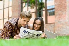 Couples gais détendant avec le papier sur l'herbe Photo libre de droits