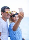 Couples gais dans des lunettes de soleil prenant le selfie mobile Image stock