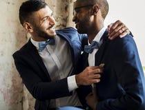 Couples gais dans le smoking de bleu marine se reposant ensemble Photographie stock libre de droits