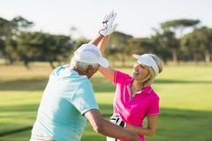 Couples gais de golfeur donnant la haute cinq Image libre de droits