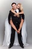 Couples gais de mariage ayant l'embrassement de marié de jeune mariée d'amusement Image libre de droits