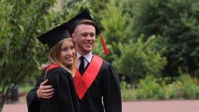 Couples gais des diplômés tenant des diplômes et posant pour l'appareil-photo, étudiants banque de vidéos