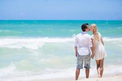 Couples gais embrassant et posant sur la plage un jour ensoleillé Image stock