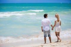 Couples gais embrassant et posant sur la plage un jour ensoleillé Image libre de droits