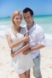 Couples gais embrassant et posant sur la plage un jour ensoleillé Images stock