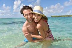 Couples gais en eau de mer clair comme de l'eau de roche Photographie stock libre de droits