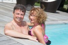 Couples gais et avec du charme ayant l'amusement en piscine Image stock