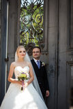 Couples gais et romantiques des nouveaux mariés posant près de la vieille porte Images stock