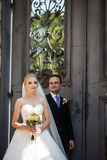 Couples gais et romantiques des nouveaux mariés posant près de la vieille porte Photos libres de droits