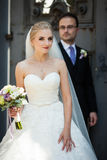 Couples gais et romantiques des nouveaux mariés posant près de la vieille porte grise Images libres de droits