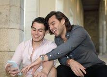 Couples gais heureux souriant avec leur téléphone portable photographie stock