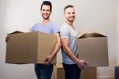 Couples gais heureux tenant des boîtes photos stock