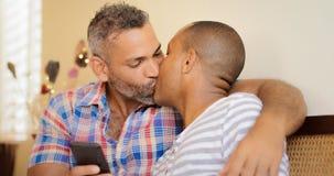Couples gais heureux tenant le téléphone portable et des baisers Photos libres de droits