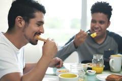 Couples gais mangeant le petit déjeuner à la maison pendant le matin Images libres de droits