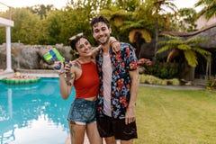 Couples gais par la piscine avec l'arme à feu d'eau Photos stock