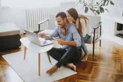 Couples gais recherchant l'Internet sur l'ordinateur portable à la maison photo stock