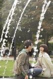 Couples gais riant sur le bord de fontaine Photographie stock