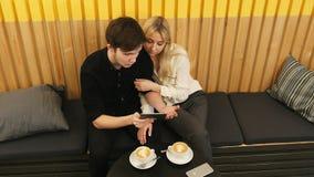 Couples gais se reposant au café et websurfing sur le comprimé Photos libres de droits
