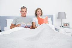 Couples gais se reposant dans des livres de lecture de lit Photo stock
