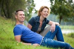Couples gais se reposant sur l'herbe dehors Images stock