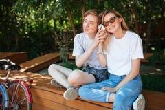 Couples gais se reposant sur le banc en parc et musique heureusement de écoute sur le téléphone portable avec deux bicyclettes to Image libre de droits