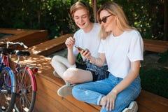 Couples gais se reposant sur le banc en parc et regardant heureusement dans le téléphone portable avec deux bicyclettes tout près Photo libre de droits