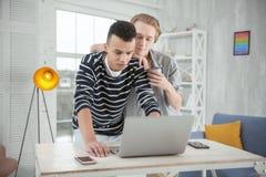 Couples gais songeurs estimant l'ordinateur portable Photos stock