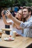 Couples gais tenant le téléphone intelligent tout en se reposant au café de trottoir Photo libre de droits
