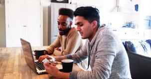 Couples gais utilisant l'ordinateur portable tout en ayant le café banque de vidéos