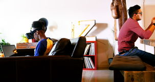 Couples gais utilisant le casque de réalité virtuelle, l'ordinateur portable et le comprimé numérique dans le salon banque de vidéos