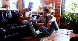 Couples gais utilisant le comprimé numérique et le téléphone portable clips vidéos
