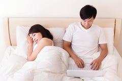 Couples gais utilisant le pavé tactile dans le lit Image libre de droits
