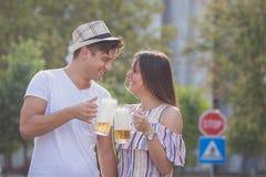 Couples grillant avec de la bière extérieure Photos stock