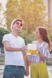 Couples grillant avec de la bière extérieure Photographie stock libre de droits