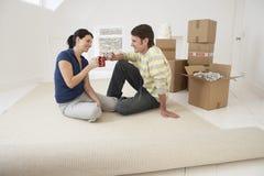 Couples grillant des tasses de café dans la nouvelle maison photographie stock