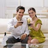Couples grillant le vin rouge célébrant l'anniversaire Image libre de droits